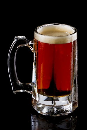 frozen mug with an irish red ale beer isolated on a black background photo