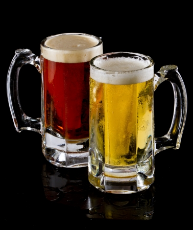 ale: two frozen beer mugs with a lager and a red ale on a dark background Stock Photo