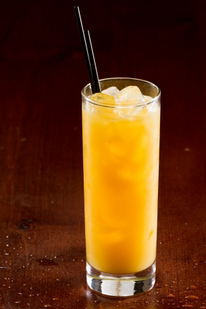 alcohol screwdriver: screwdriver drink with a bright yellow glow served on a dark bar