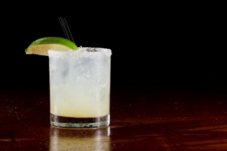 fresh lime juice margarita served on the rocks in a dark restaurant