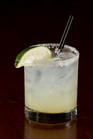 fresh lime juice margarita served on the rocks in a dark restaurant photo