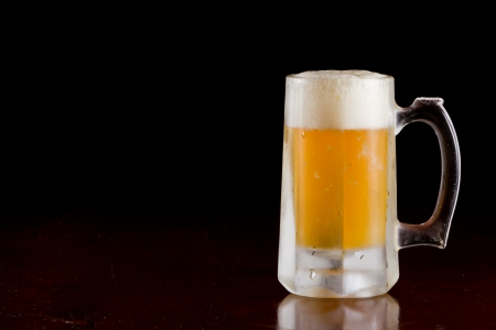 cold beer served in a frozen mug on a bar top isolated on a black background photo
