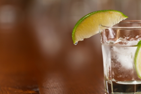 glass of silver tequila served neat with fresh sliced lime on a out of focus bar Stock Photo - 19894186