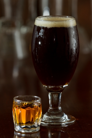 an ounce: beer and a shot of whiskey served on a busy out of focus bar Stock Photo