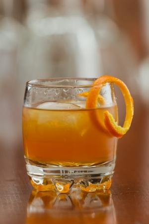 오렌지 술 장식으로 오렌지 트위스트와 함께 바위에 제공