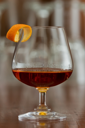brandy snifter filled with an orange liquor served on a busy bar top garnished with an orange twist
