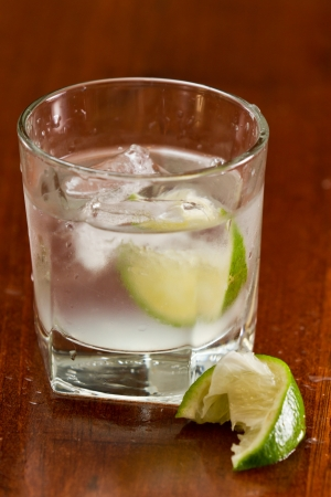 glass of silver tequila served neat with fresh sliced lime on a out of focus bar Stock Photo - 19894171