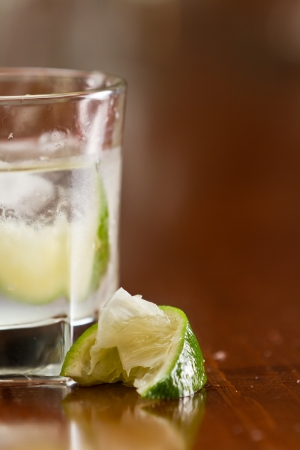 glass of silver tequila served neat with fresh sliced lime on a out of focus bar Stock Photo - 19894188