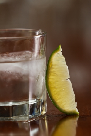 glass of silver tequila served neat with fresh sliced lime on a out of focus bar Stock Photo - 19894173