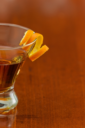 stemless martini glass with an orange liquor served on a busy bar top garnished with an orange twist photo