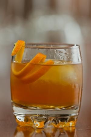 orange liquor served on the rocks with an orange twist as a garnish photo