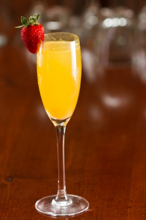 sparkling wine served in a flute with fresh orange juice garnished with a red strawberry on a out of focus bar top