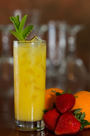 alcohol screwdriver: fresh orange juice with vodka served on a busy out of focus bar and fresh fruit on the side Stock Photo