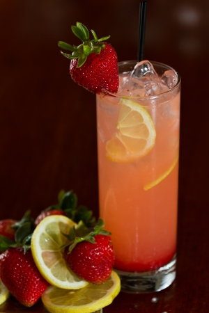 strawberry lemonade served with vodka in a busy out of focus bar with fresh ingredients next to it photo