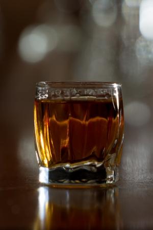 closeup of a shot glass full of bourbon served on a bar top photo