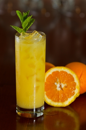 alcohol screwdriver: fresh orange juice with vodka served on a busy out of focus bar and slices of fruit on the side Stock Photo