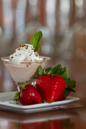 glass topped: small martini glass with dark chocolate mousse topped with whipped cream and a mint leaf served with fresh berries Stock Photo