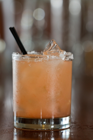 closeup of a salty dog drink served in a short glass on a busy out of focus bar