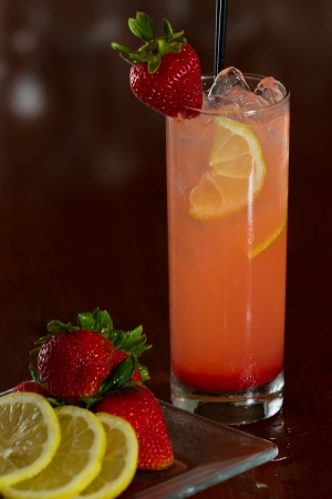 strawberry lemonade served with vodka in a busy out of focus bar with fresh ingredients next to it