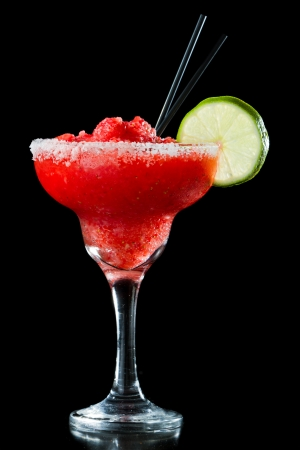 frozen strawberry margarita isolated on a black background garnished with a salt rim and a lime wheel