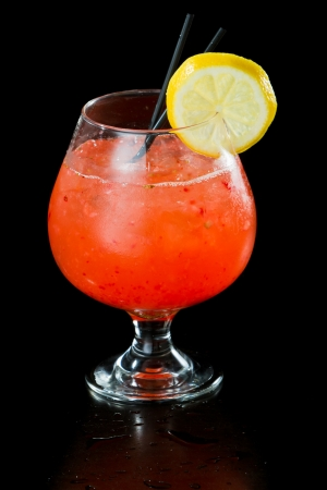 strawberry lemonade isolated on a black background served in a brandy snifter garnished with a lemon wheel photo