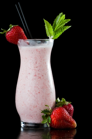 strawberry milk shake isolated on a black background garnished with fresh green mint