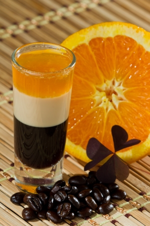b 52 shots layered and served with an orange and coffee beans on a wooden place mat photo
