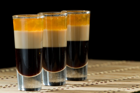 b 52 shots layered and served with coffee beans on a wooden place mat photo