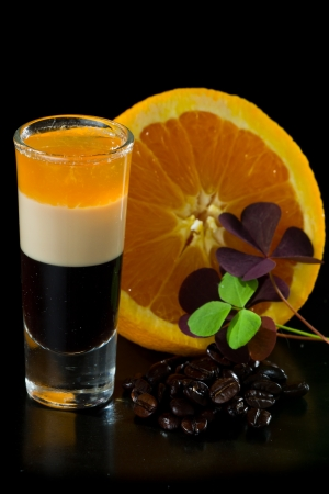 b 52 shots layered and served with an orange and coffee beans on a isolated black background photo