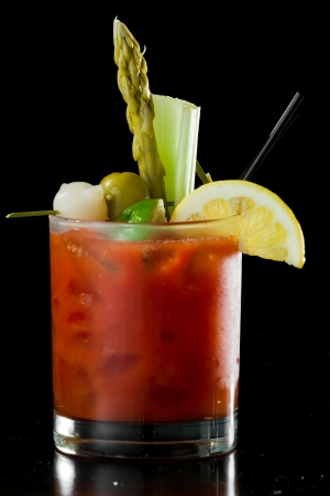 spicy Bloody Mary served on a dark bar garnished with pickled veggies and a lemon