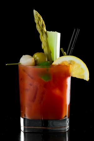 spicy Bloody Mary served on a dark bar garnished with pickled veggies and a lemon photo
