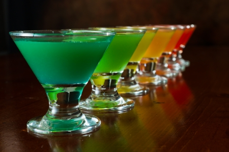 rainbow cocktail: classic bar flair trick, rainbow colored juice served in multiple shot glasses in a row Stock Photo