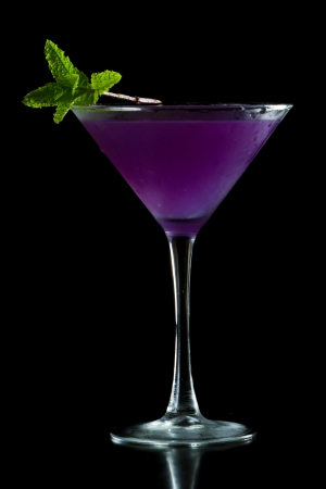 refreshing purple martini served isolated on a black background garnished with fresh mint