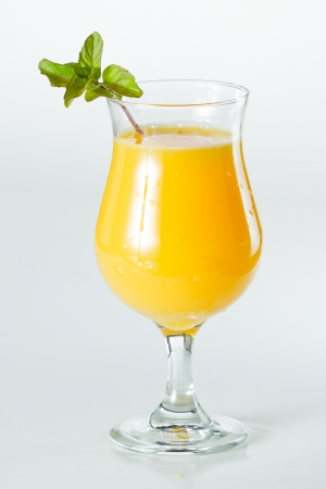 closeup of a glass filled with fresh orange juice garnished with fresh mint isolated on a white background Imagens