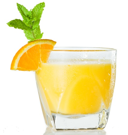 alcohol screwdriver: closeup of a glass filled with fresh orange juice garnished with an orange slice and fresh mint isolated on a white background