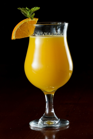 alcohol screwdriver: closeup of a glass filled with fresh orange juice garnished with fresh mint and an orange slice
