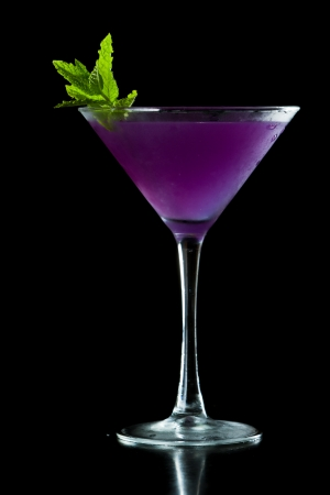 refreshing purple martini served isolated on a black background garnished with fresh mint photo