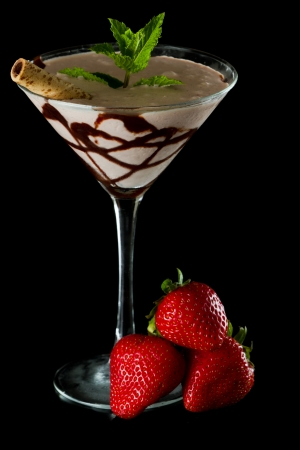 chocolate martini served isolated on a black background with chocolate swirl and a wafer stick photo