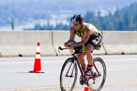 exert: COEUR D ALENE, ID -  JUNE 23: Paul Lee, Triathlete on the bike part of the ironman triathlon, June 23 2013 in Coeur d Alene Idaho