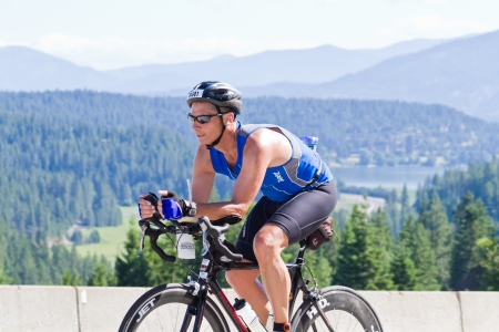 exert: COEUR D ALENE, ID -  JUNE 23: Triathlete on the bike part of the ironman triathlon, June 23 2013 in Coeur d Alene Idaho