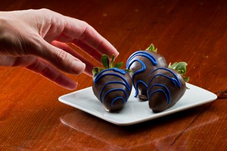 chocolate covered strawberries: Primer plano de deliciosas fresas cubiertas de chocolate servido en un plato blanco