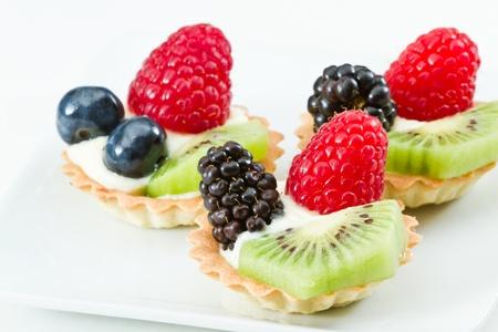 bite size fruit tarts with fresh fruit served on a white background