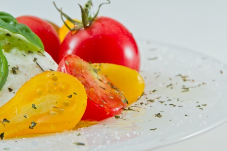 closeup of a fresh heirloom tomato and buffalo mozzarella salad isolated on a white background garnished with fresh green basil photo