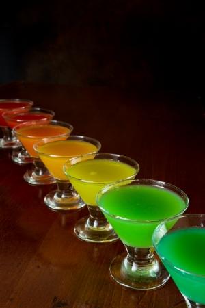 rainbow cocktail: bar classico stile trucco, arcobaleno succo colorato servito in diversi bicchierini di fila Archivio Fotografico