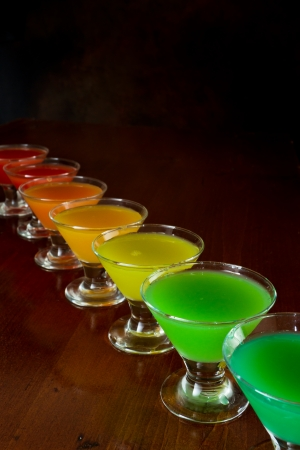 the flair: classic bar flair trick, rainbow colored juice served in multiple shot glasses in a row Stock Photo