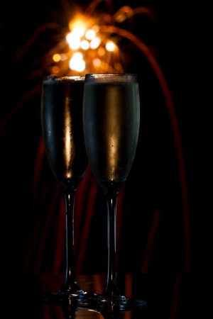 dark scene with two glasses of champagne and fireworks in the\ background