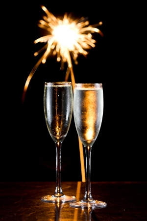 flutes: dark scene with two glasses of champagne and fireworks in the background Stock Photo