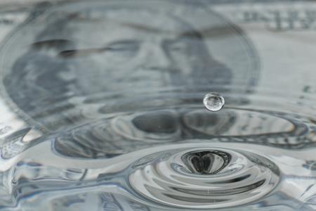 cash money: gotas de agua y ondulaciones con un billete de cien dólares como fondo y la reflexión