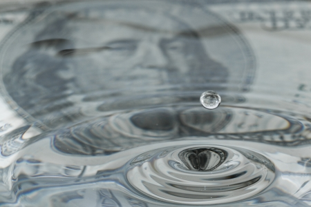 liquid state: water drops and ripples with a one hundred dollar bill as a background and reflection