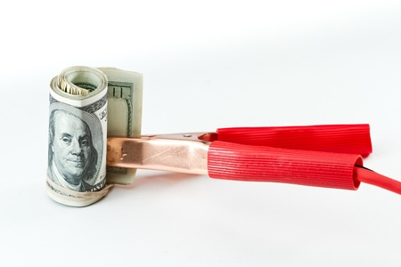 fiscal cliff: booster cables attached to a roll of one hundred dollar bills on a white background